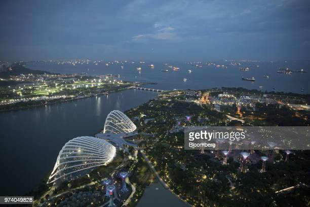 The Gardens by the Bay and ships sitting offshore in the Singapore Strait are illuminated at dusk in Singapore on Wednesday June 13 2018 Tourism as...