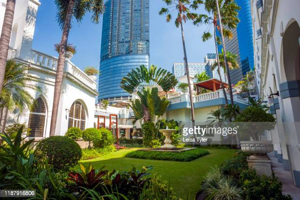 The gardens of the Hotel Majapahit, a historical hotel built by the Sarkies Brothers in 1910, with the sky scrapers of Surabaya in the background,...