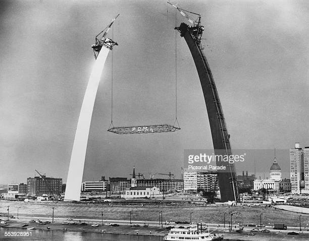 The Gateway Arch monument under construction in St Louis Missouri USA circa 1964 Creeper derricks are placing a temporary scissors truss between the...