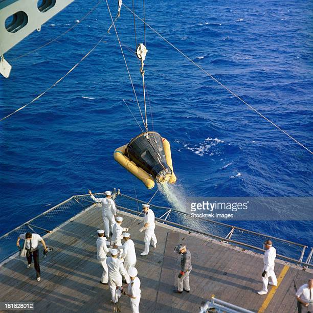 The Gemini-3 spacecraft is hoisted aboard the USS Intrepid during recovery.