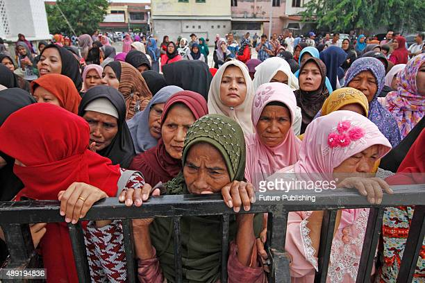 The general public watches as punishment is meted out during a public caning ceremony outside a mosque on September 18 2015 in Banda Aceh Indonesia...