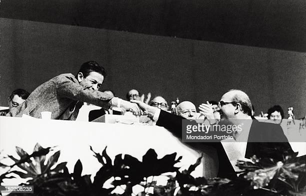 The General Secretary of the Italian Communist Party Enrico Berlinguer shaking hands with the socialist Bettino Craxi during a political congress...