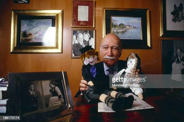 The general secretary of the Italian Social Movement Giorgio Almirante sitting at the desk holding two rag dolls Italy 1980s