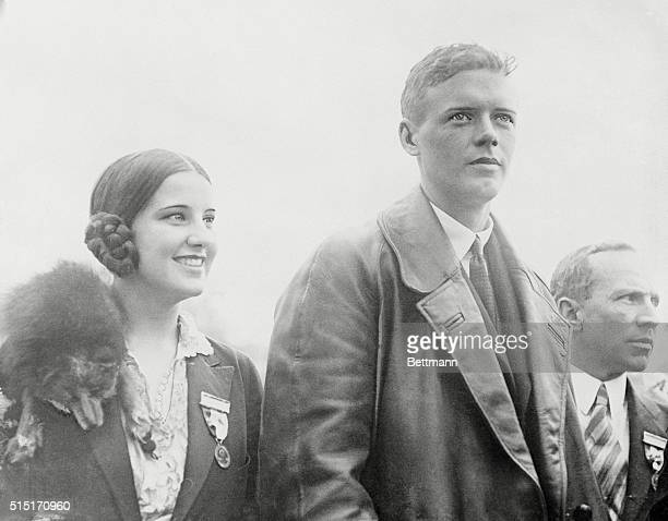 The gentleman to the right can easily be recognized as Colonel Charles A. Lindbergh, first man to fly across the Atlantic from New York to Paris. If...