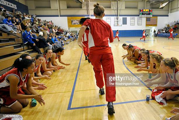 The George Mason junior varsity basketball team kneel and beat the floor as the varsity team heads out onto the court for warm ups The team took a...