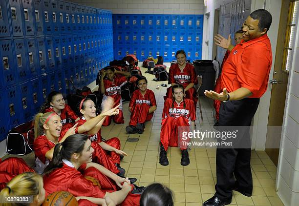 the George Mason varsity basketball coach LaBryan Thomas right jokes with his team in the locker room just before heading out for warm ups The team...