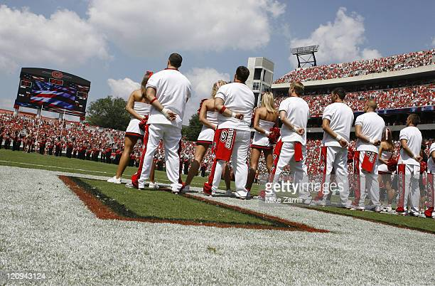 The Georgia cheerleaders pause during the national anthem before the game between the University of Georgia Bulldogs and University of...