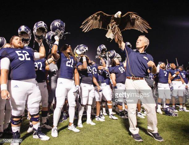 The Georgia Southern Eagles celebrate their win over the University of Massachusetts as handler Steve Hein hoists Freedom the team's live mascot on...