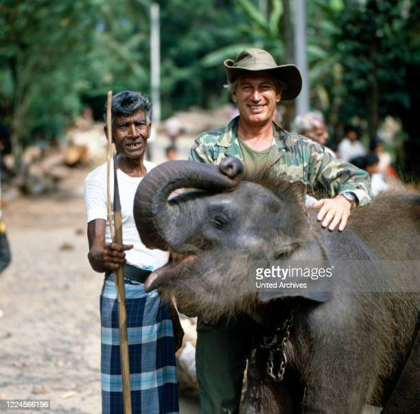 The german actor Siegfried Rauch at the set for 'Death Stone' with a local and an elefant, Sri Lanka 1986.