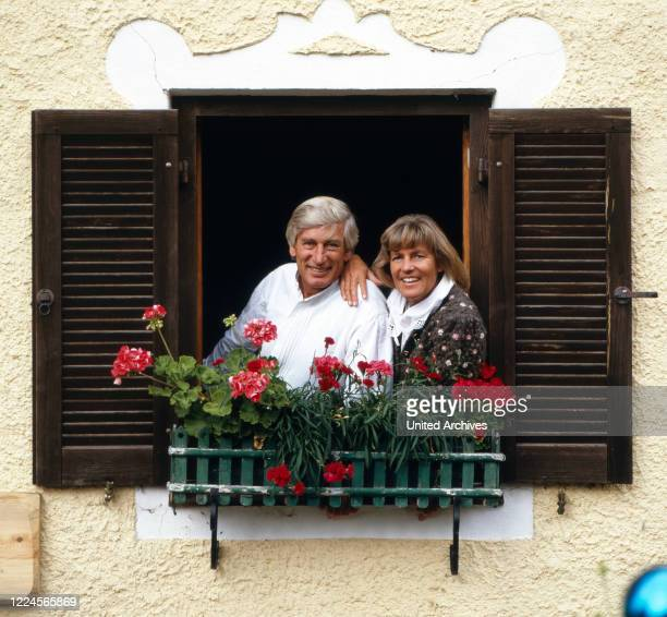 The german actor Siegfried Rauch is looking together with his wife out of the window, Germany, 1980.