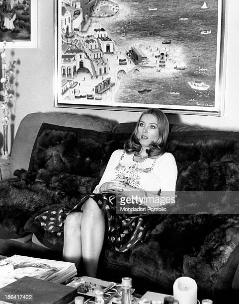 The German actress Barbara Bouchet born Barbara Gutscher and naturalized Italian sits in the sitting room behind her a naive painting representing a...