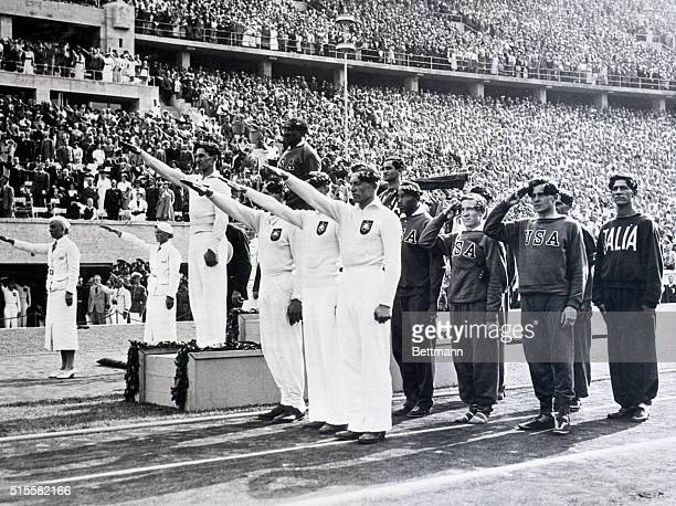 The German, American, and Italian olympic relay teams stand before the crowd at a medal ceremony. The American team composed of Ralph Metcalfe, Jesse...
