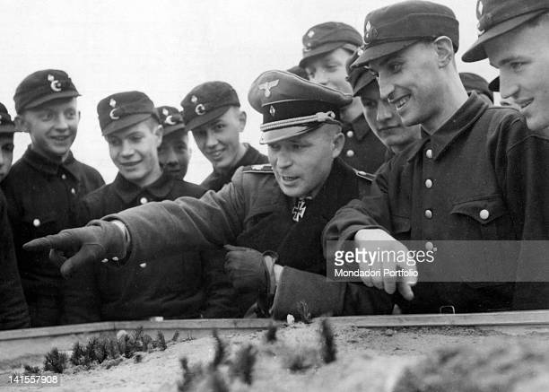 The German captain Gerhard Hein decorated with the Iron Cross illustrates on a relief model the various war operations to an audience of young people...