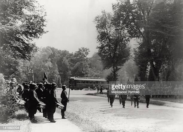 The German Chancellor Adolf Hiltler and the Field Marshal Hermann Goring are saluted by a military band They are leaving the CompiFgne Forest on the...