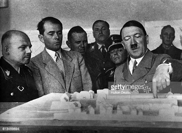 The German Chancellor Adolf Hitler accompanied by Governor Saukel on his right and Albert Speer discusses plans for a new administration building for...
