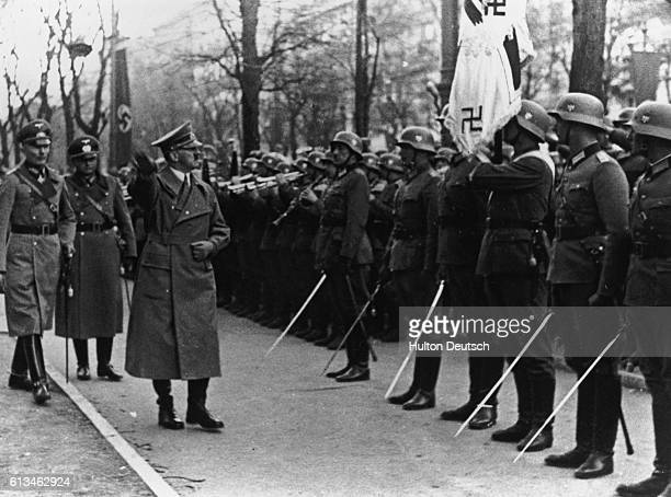 The German Chancellor Adolf Hitler inspects a guard of honour of German troops in Vienna following their invasion of Austria and its incorporation...