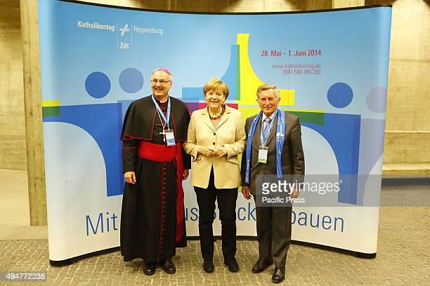 REGENSBURG BAVARIA GERMANY The German Chancellor Angela Merkel pose for the camera together with Rudolf Voderholzer the bishop of Regensburg and...