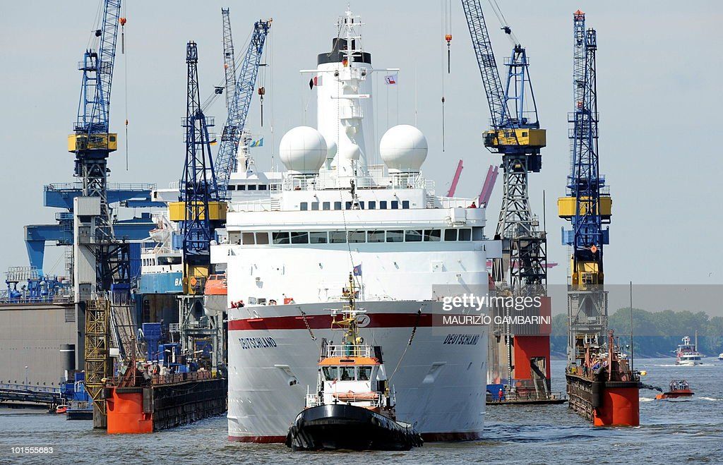 The German cruise ship 'MS Deutschland' is brought to the docks of the 'Blohm + Voss' shipyard in Hamburg, northern Germany, on June 2, 2010. Rescuers had evacuated around 600 tourists and crew from the ship docked in a Norwegian fjord on May 30, 2010, after its engine room caught fire.