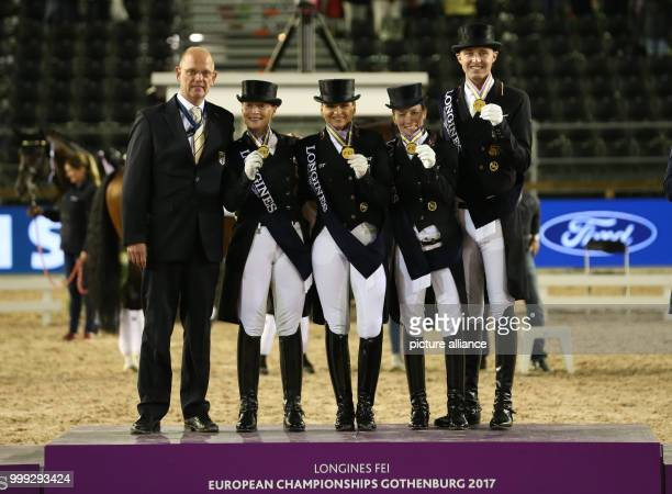 The German dressage team with Sonke Rothenberger , Helen Langehanenberg, Dorothee Schneider and Isabell Werth celebrating with Klaus Roeser, coach of...