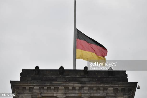 The German flag flies at halfmast at the Reichstag building that houses Germany's Bundestag lower house of parliament in Berlin on May 24 2017 At...