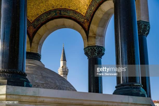 The German Fountain Alman Çemesi located on Sultanahmet Square Sultanahmet Meydan a minaret of Firuz Aa Mosque in the distance