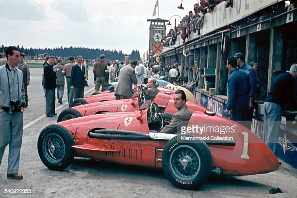 The German Grand Prix Nürburgring August 2 1953 World Champion Alberto Ascari sits in his Ferrari 500/F2 in front of the pits with Mike Hawthorn in...