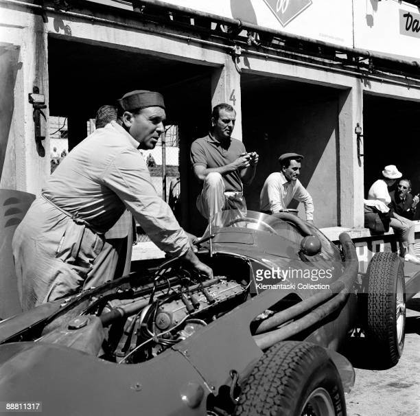 The German Grand Prix; Nürburgring, August 4, 1957. The well-liked Franco-American driver Harry Schell waits while a Maserati mechanic sees to the...