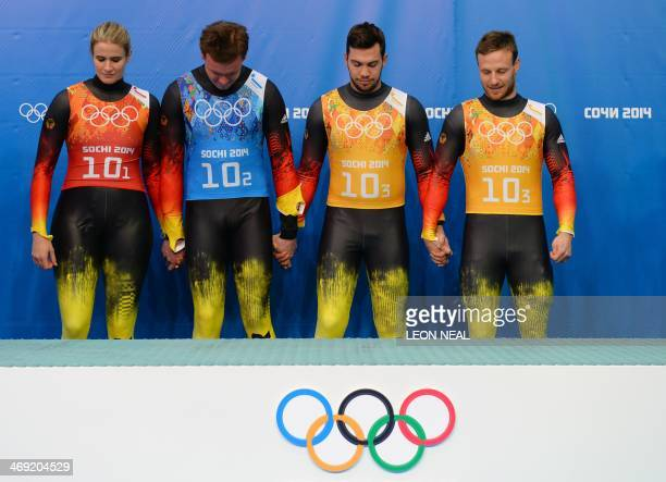 The German Luge Team of Natalie Geisenberger Felix Loch Tobias Wendl and Tobias Arlt hold hands at the Luge Team Relay Flower Ceremony at the Sliding...