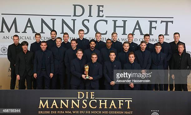 The German natioal football team pose with the FIFA World Cup Winners Trophy prior to the movie premiere 'Die Mannschaft' at Sony Center Berlin on...