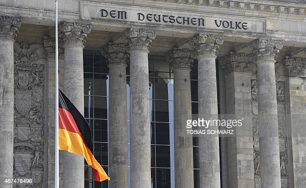 The German national flag flies on March 25 2015 at halfmast at the Reichstag building housing the Bundestag in Berlin to commemorate the victims of...