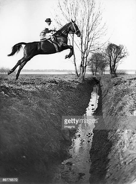 The german show jumper Axel Holst during a jump over a moat at a morning ride across the fields Photograph Around 1930