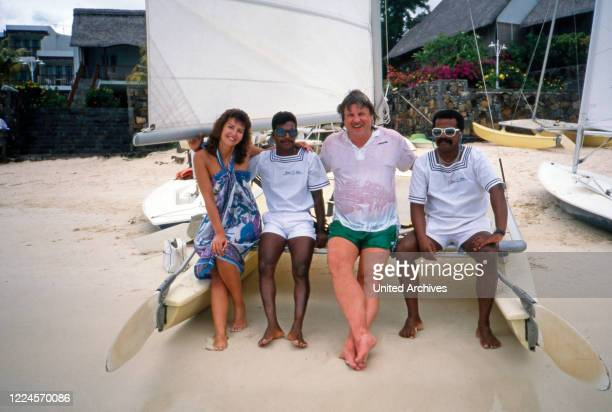 The German singer Klaus Baumgart poses with locals and his wife Ilona SchulzBaumgart in front of a small catamaran on vacation probably on the...