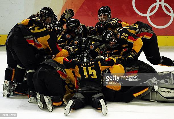 The German team congratulate Nikola Holmes of Germany after she scored the winning goal in the shoot out during the women's ice hockey 5th & 6th...