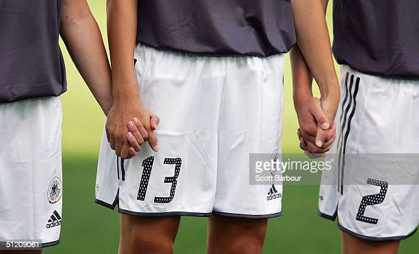 The German team hold hands as they sing the national anthem before the women's football semifinal match between USA and Germany on August 23 2004...