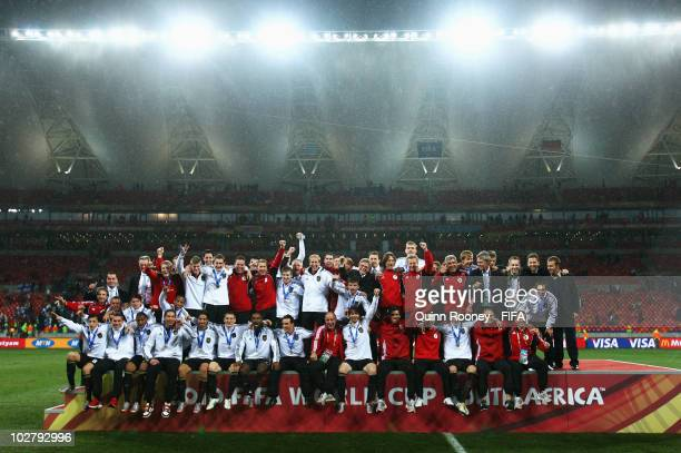 The Germany team celebrate with their bronze medals after coming third during the 2010 FIFA World Cup South Africa Third Place Playoff match between...
