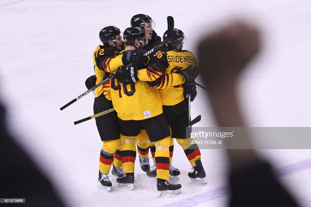 The Germany team celebrates after Germany's Yannic Seidenberg scored the winning goal in overtime in the men's play-offs qualifications ice hockey match between Switzerland and Germany during the Pyeongchang 2018 Winter Olympic Games at the Kwandong Hockey Centre in Gangneung on February 20, 2018. / AFP PHOTO / Jung Yeon-je