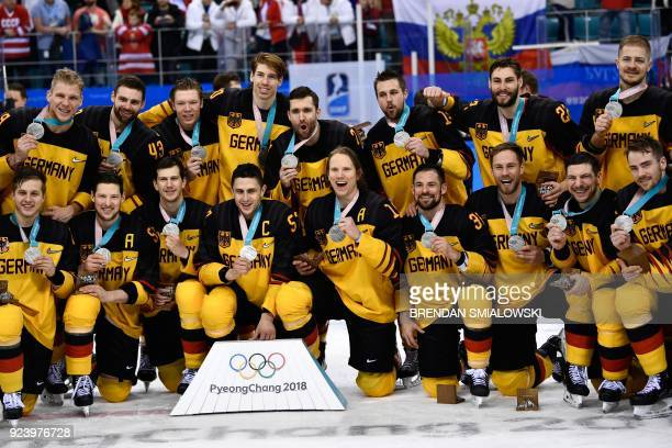 The Germany team poses with their silver medals after the medal ceremony after the men's gold medal ice hockey match between the Olympic Athletes...