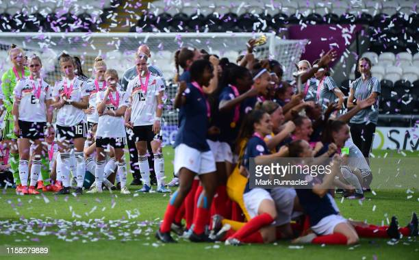 The Germany Women's U19 squad and coaches look on as the France Women's U19 team lift the European Championship trophy during the UEFA Women's...