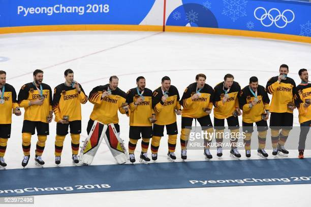 The Germany's players pose with their silver medals on the podium during the medal ceremony after the men's gold medal ice hockey match between the...