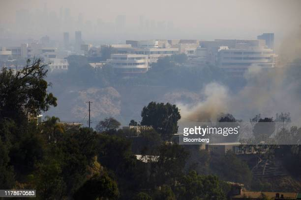 The Getty Center stands as smoke rises behind homes during a brush fire in Los Angeles California US on Monday Oct 28 2019 A fastmoving brush fire...
