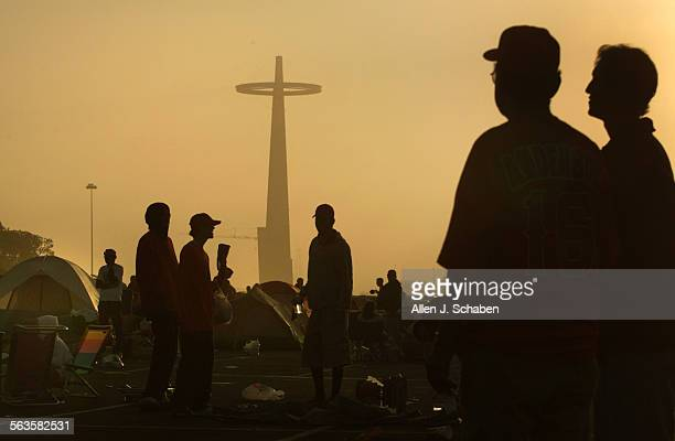 The giant Anaheim Angels sign stands tall as golden morning sunshine cuts through the fog silhouetting thousands of Angels fans including Mike Platta...