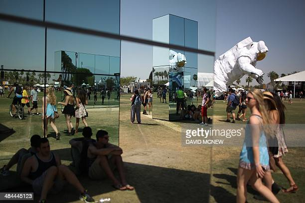 The giant inflated astronaut art piece Escape Velocity moves past people reflected among the mirrors of an art exhibit at the Coachella Valley Music...