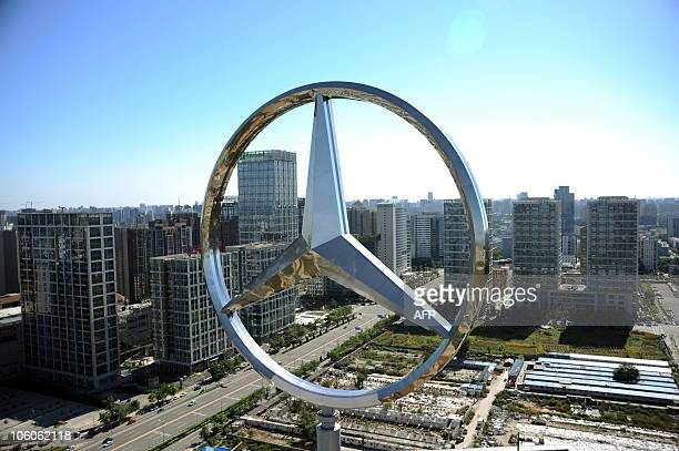 The giant logo of German vehicle maker Daimler's MercedesBenz sits on the top of its head office building in Beijing on October 11 2010 Booming auto...