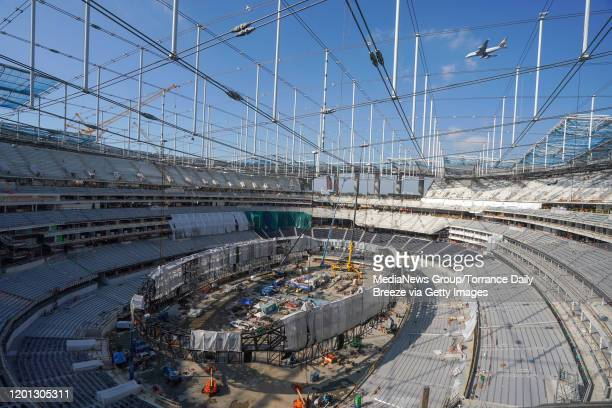 The giant Oculus 2-sided video board is being assembled inside on the floor of SoFi Stadium as roofing panels begin to cover the entire structure as...