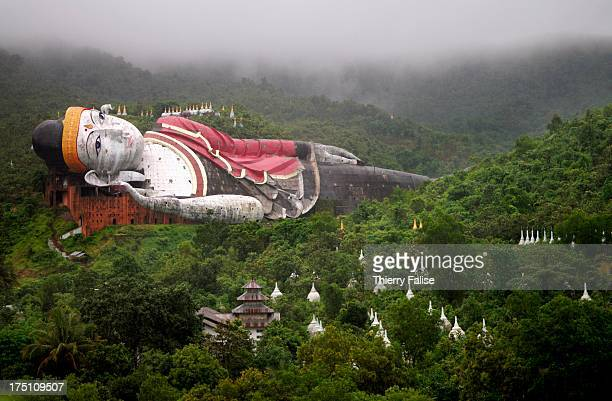 The giant reclining Buddha of the Zinathukha pagoda surrounded by the jungle and stupas This reclining Buddha of which the concrete structure is 200...