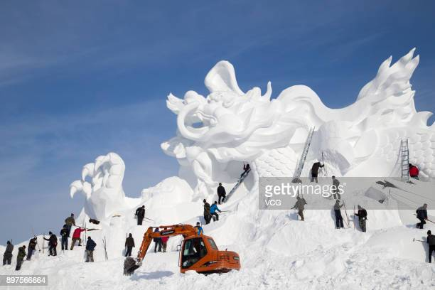 The giant snow sculpture featuring a dragon for Jingyuetan Vasaloppet International Skiing Festival is built by a team of about 100 snow carvers at...