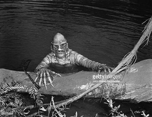 The 'gill man' a scaly creature with webbed and clawed hands rises from the water in the film 'Creature from the Black Lagoon' directed by Jack...