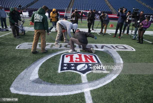 The Gillette Stadium field crew applies paint to the AFC Divisional Playoff round logo ahead of Sunday's game between the New England Patriots and...