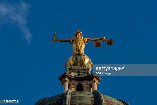 The gilt bronze sculptor of Lady Justice by F. W. Pomeroy holding a sword on her right hand and the scales of justice on her left on the dome above...