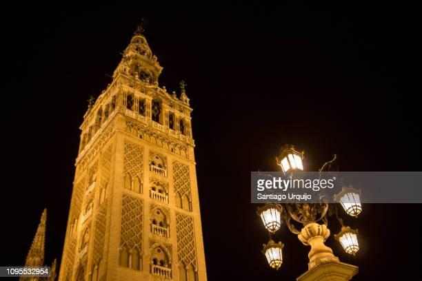 the giralda of the cathedral of seville at night - la giralda fotografías e imágenes de stock